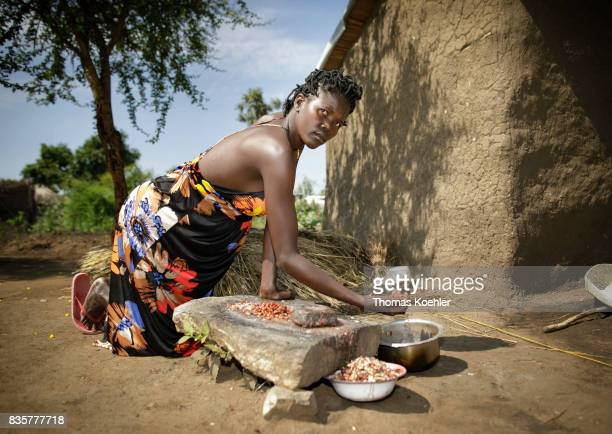 An African woman prepares food in front of her hut at the Rhino Refugee Camp Settlement in northern Uganda The area is home to about 90000 refugees...