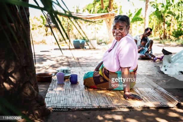 わらのマットに座っているアフリカ人の女性が、カメラに戻ってポートレートを探している - ザンビア ストックフォトと画像