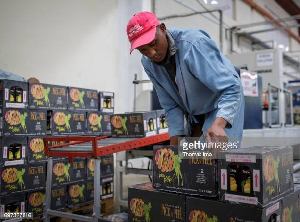 An African worker is stacking tetrapacks in a warehouse Production of juice at beverage manufacturer Kevian Kenya Ltd on May 18 2017 in Thika Kenya