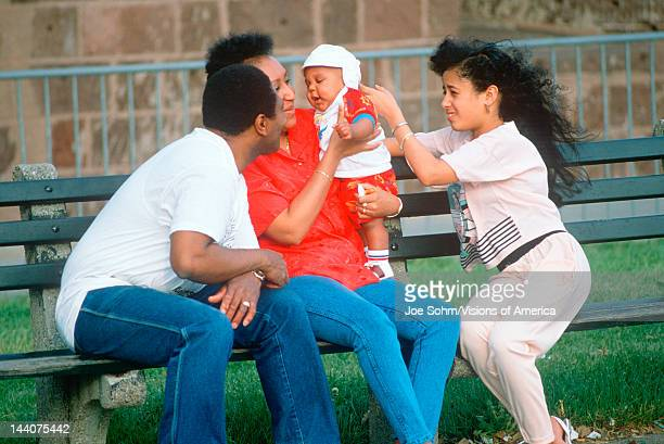 An AfricanAmerican family playing with a baby on a park bench NY City