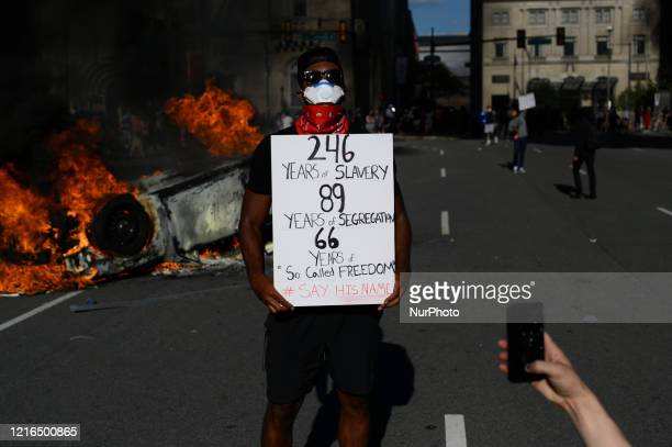 An AfricanAmerican male poses with a sing in front of burning and overturned police cruiser as protestors clash with police near City Hall in...