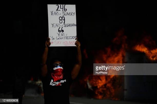 An AfricanAmerican male poses with a sing in front of burning police vehicles as protestors clash with police near City Hall in Philadelphia PA on...