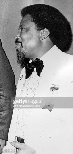 An AfricanAmerican man in a white tuxedo and bow tie with an afro hair style 1945