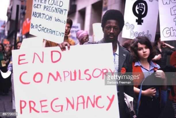 An AfricanAmerican man participates in a protest march and carries a sign reading 'End Compulsory Pregnancy' at reproductive rights demonstration in...