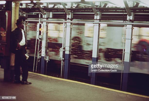 An African-American man stands on a subway station platform as a subway train car, covered in graffiti, passes by in New York City, New York, May,...