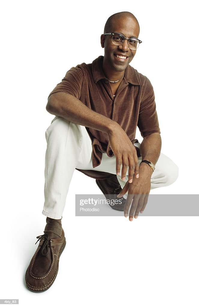 an african-american man wearing a brown velvet shirt and white pants with brown socks and shoes smiles at the camera as he rests his arms on his knees : Foto de stock