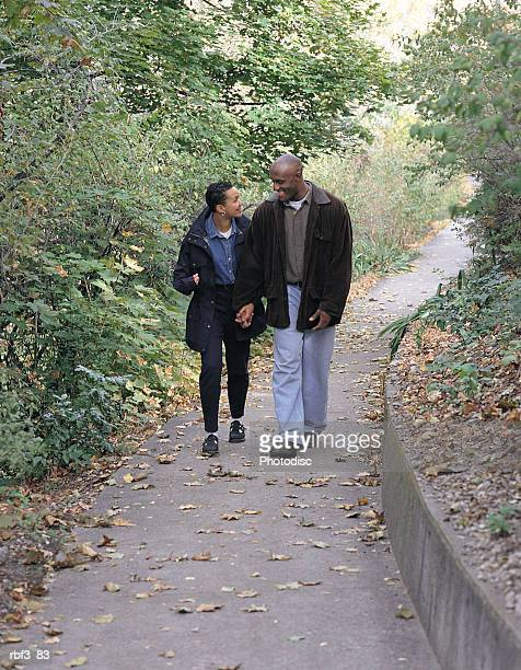 an african-american man wearing denim jeans and a brown coat walks down a green path with an african-american woman wearing black pants and a denim shirt as they hold hands and talk - pants down woman stock pictures, royalty-free photos & images