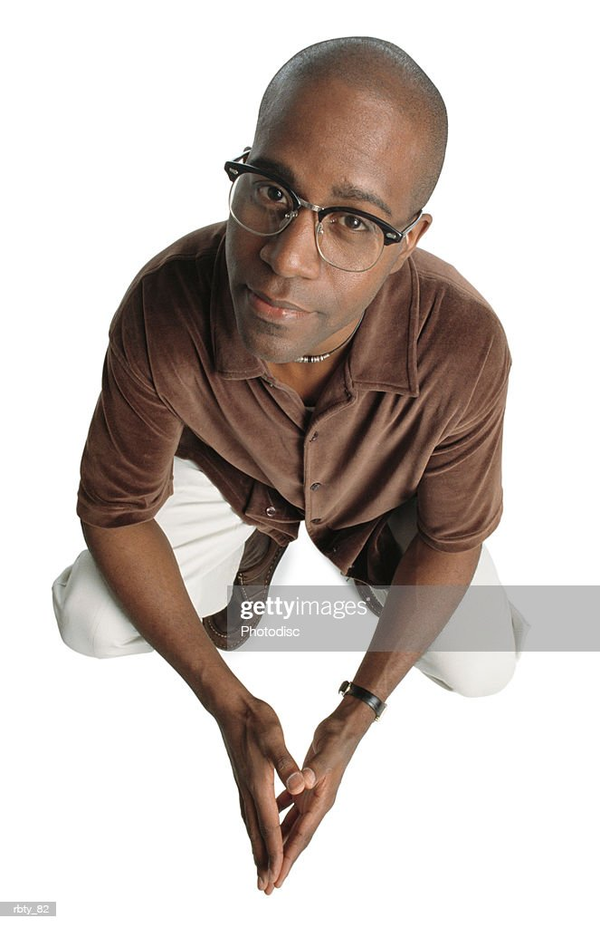 an african-american man wearing white pants and a brown velvet shirt and glasses puts his hands together as he crouches and looks up toward the camera : Foto de stock