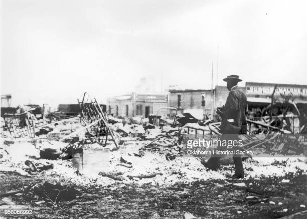 An African-American man with a camera looking at the skeletons of iron beds which rise above the ashes of a burned-out block after the Tulsa Race...