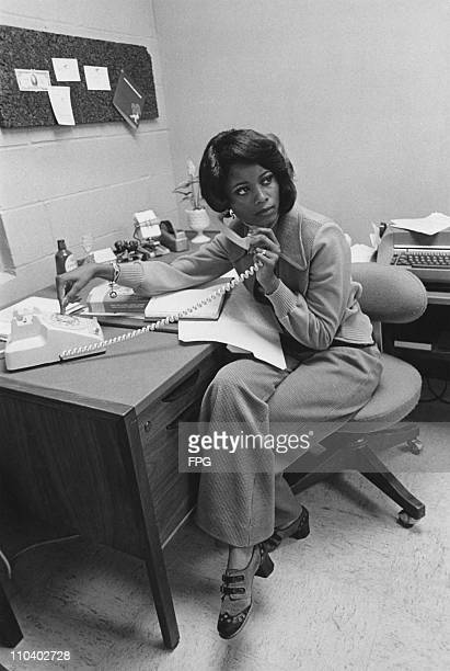 An AfricanAmerican office worker takes a phone call USA circa 1975