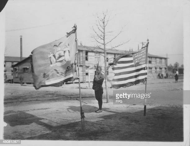 An AfricanAmerican soldier of the 369th Infantry Regiment formerly the 15th New York National Guard guarding the US flag at Camp Upton during World...