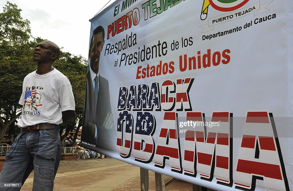 An African-American stands next to a huge banner during the inauguration ceremony of US President Barack Obama on January 20, 2009, in the main square of the municipality of Puerto Tejada, Cauca department, Colombia. AFP PHOTO/Luis Robayo