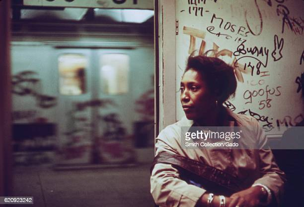 An AfricanAmerican woman sits inside a subway car which has been marked with extensive graffiti New York City New York 1973 Image courtesy National...