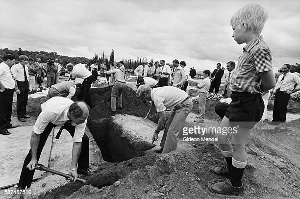 An Afrikaner boy watches as multiple graves are filled in during a funeral for a family of farmers who were killed by a land mine set by the African...