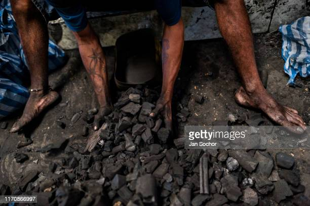 An AfroColombian man divides charcoal into small plastic bags to be sold in the Bazurto openair market on December 19 2017 in Cartagena Colombia