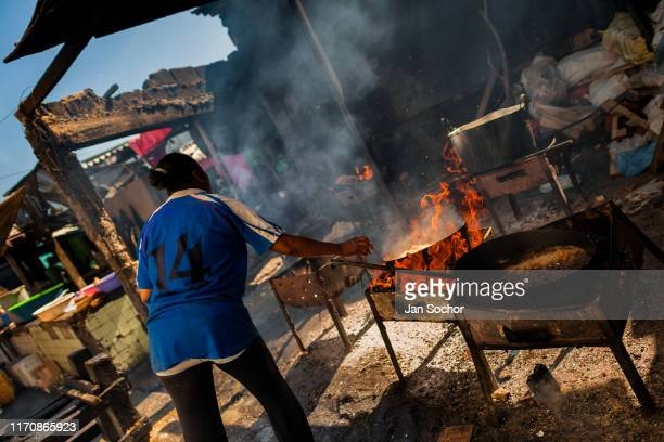 An AfroColombian woman fries fish in boiling oil in a street restaurant in the Bazurto openair market on December 19 2017 in Cartagena Colombia