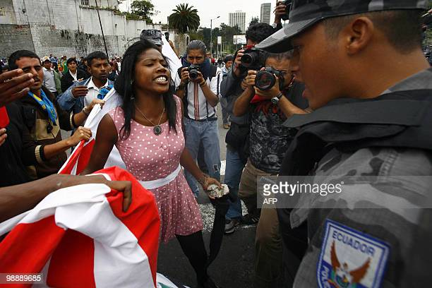 An AfroEcuadorean woman argues with police guarding a fence in front of the National Assembly in Quito on May 5 2010 in protest of a proposed water...