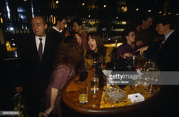 An afterwork Christmas party at Coates Wine Bar on London Wall gathers energy after nine o'clock pm at a table near the bar A group of three girls...
