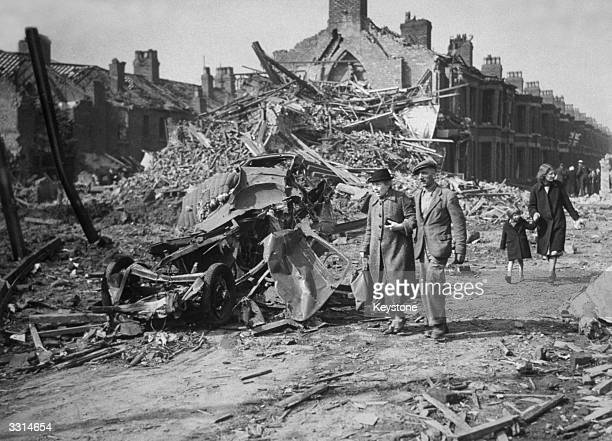 An aged Liverpool couple gaze at the ruins of another bombed home as they walk through the street the morning after a bombing raid