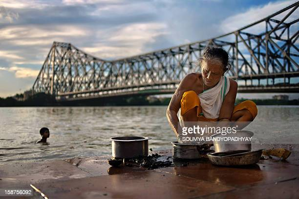 An aged woman washes utensils at mullick ghat on river ganges in kolkata while afternoon sunlight falls on her. Famous howrah bridge can be seen from...