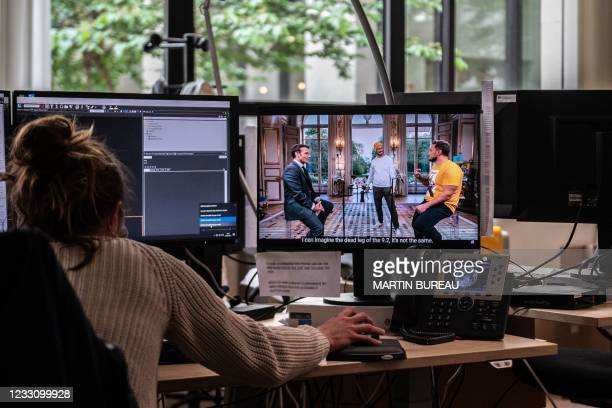 """An Agence France-Presse journalist watches France's President Emmanuel Macron as he takes part in a youtube online programme with """"McFly"""" and..."""