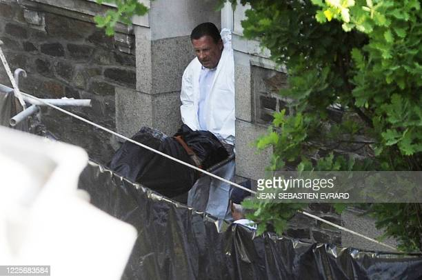 An agent carries a body on April 21 2011 in Nantes from the house of a family who disappeared 17 days ago French police launched a murder probe on...