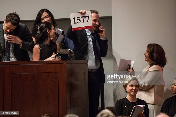 An agent holds up the winning bidding number while speaking on the phone with his client after winning an auction for the art work 'Les femmes...