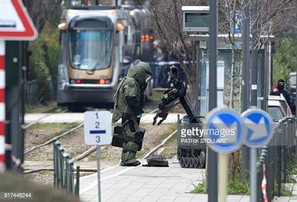 An agent of a bomb squad unit action and a robot stand next to a suspicious object at a tramway station on March 25, 2016 in Schaerbeek suburb,...