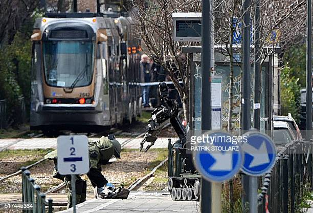 An agent of a bomb squad unit action touches a suspicious object next to a bomb squad robot at a tramway station on March 25 2016 in Schaerbeek...