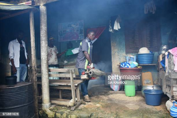 An agent of the National Institute of Public Hygene carries out fumigation in a yard in the Anyama district of Abidjan on June 9 as part of the...