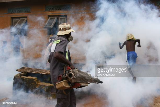 TOPSHOT An agent of the National Institute of Public Hygene carries out fumigation in the Anyama district of Abidjan on June 9 as part of the ongoing...