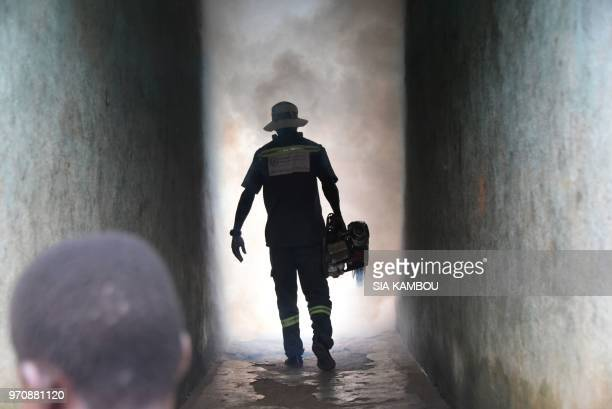 An agent of the National Institute of Public Hygene carries out fumigation in the Anyama district of Abidjan on June 9 as part of the ongoing fight...