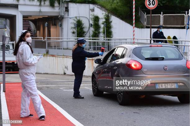 An agent scans an employee of Italian automobile manufacturer Fiat for temperature while arriving by car at the Mirafiori plant in Turin as work...