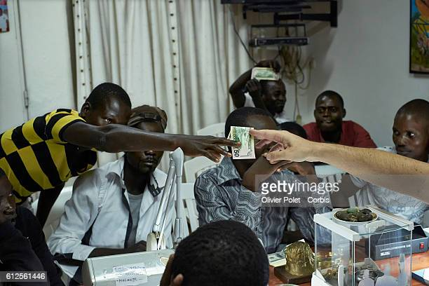 An agreement is reached and money changes hands in this picture made in a diamond buyer's office 28 March 2013 near an Angolan village not far from...