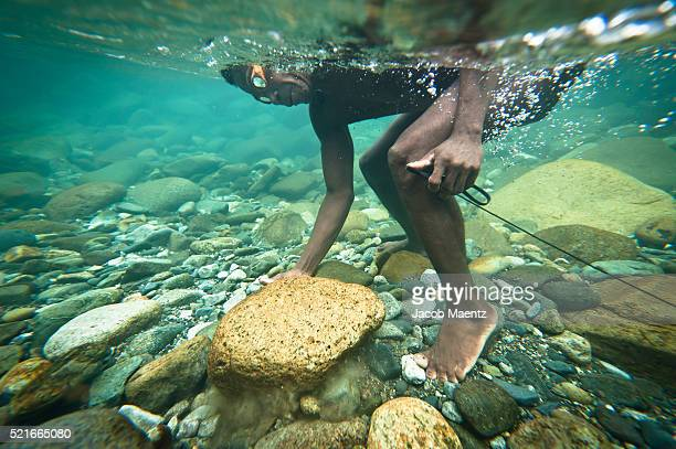 An Agta man searching for fish in the clear tropical water of the Blos River