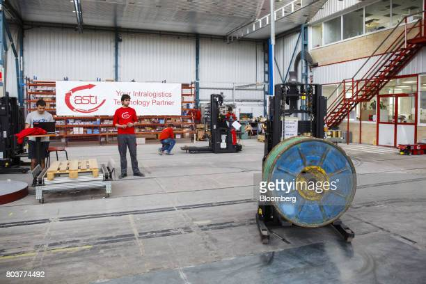 An AGV Robofast mobile robot also known as an AGV or automated guided vehicle positions a spool during testing inside the Automatismos y Sistemas de...
