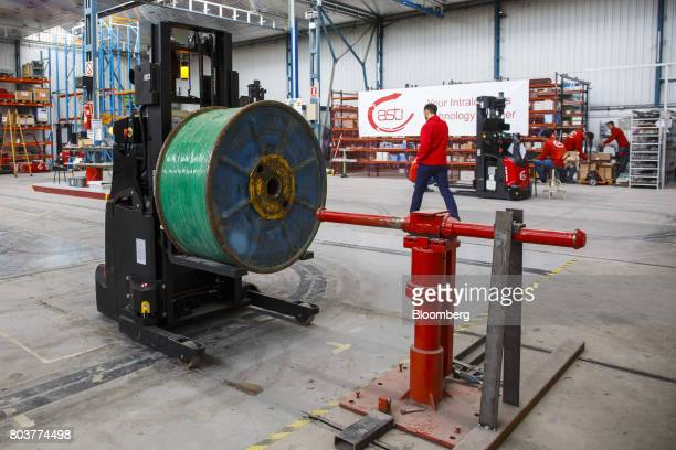 An AGV Robofast mobile robot also known as an AGV or automated guided vehicle positions a spool onto a bar during testing inside the Automatismos y...