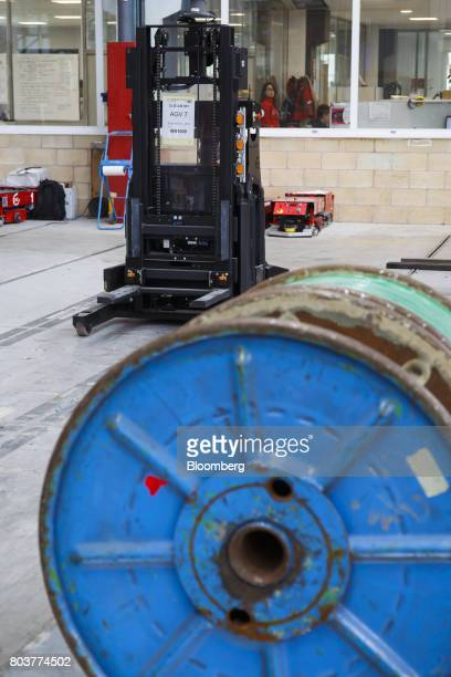 An AGV Robofast mobile robot also known as an AGV or automated guided vehicle approaches a spool during testing inside the Automatismos y Sistemas de...