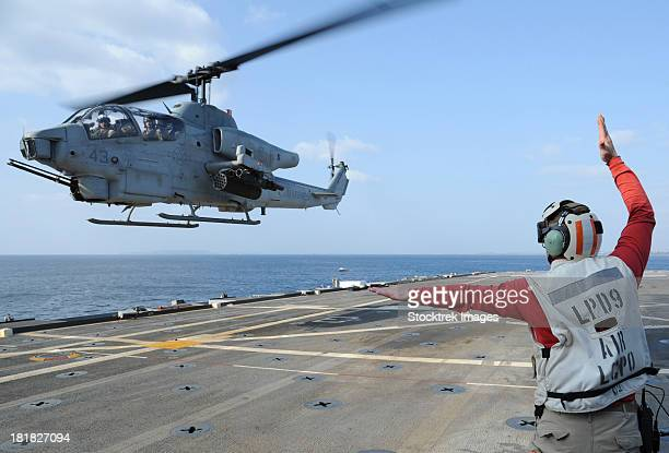 An AH-1W Cobra helicopter takes off from USS Denver.