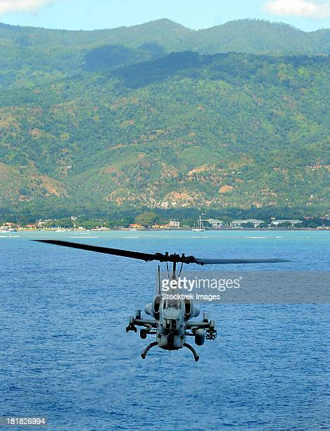 An AH-1W Super Cobra flies off the coast of Dili, East Timor.