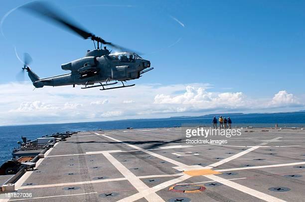 An AH-1W Super Cobra helicopter lands aboard USS Denver.