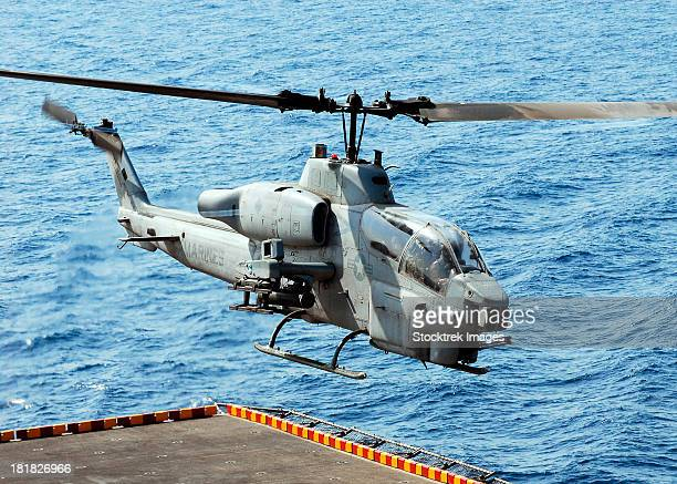 An AH-1W Super Cobra helicopter launches off the flight deck of USS Peleliu.