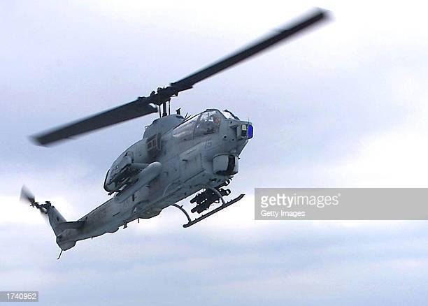 An AH1W Super Cobra helicopter prepares to land on the amphibious assault ship USS Saipan January 17 2003 at sea Four US Marines died when two...