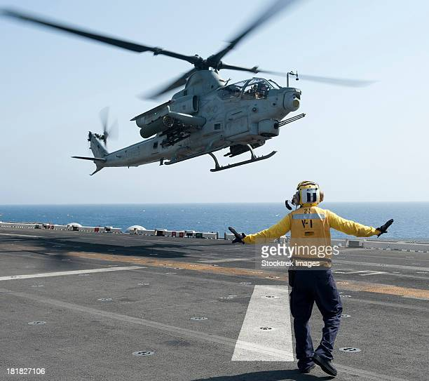 An AH-1Z Cobra helicopter takes off from the flight deck of USS Makin Island.