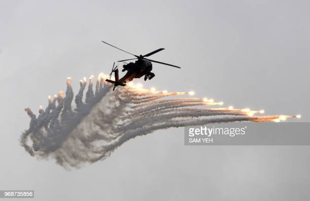 An AH64 Apache attack helicopter releases flares during the Han Kuang drill at the Ching Chuan Kang air force base in Taichung central Taiwan on June...