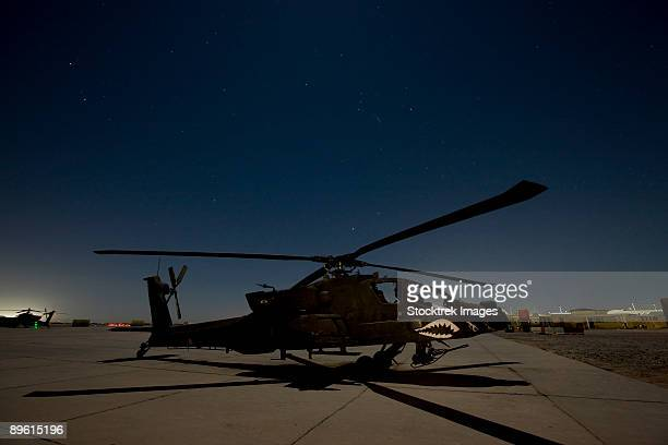 An AH-64 Apache waits on the flight line at night at Camp Speicher.