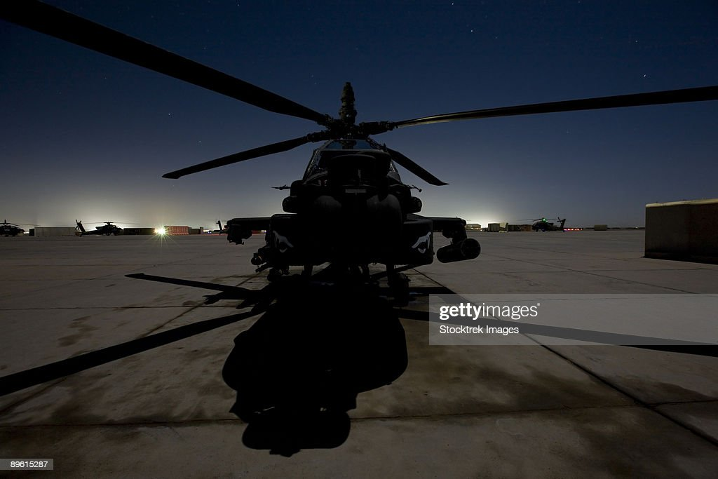 An AH-64 Apache waits on the flight line at night at Camp Speicher. : Stock Photo