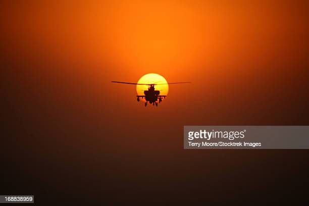 An AH-64D Apache helicopter flying into the sun over Tikrit, Iraq, during Operation Iraqi Freedom.