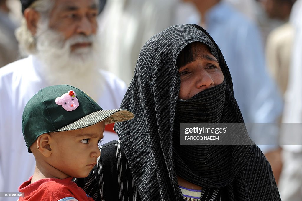 An Ahmadi Pakistani woman holding a child mourns the death of a relative in yesterday's religious attack as burials take place at an Ahmadi graveyard in Rabwa on May 29, 2010, a spiritual centre for the Ahmadi community in Pakistan about 160 kilometre west of Lahore. Victims of deadly May 28 attacks on two Pakistani mosques were buried separately after community members cancelled a mass funeral for more than 80 people, fearing further attacks. AFP PHOTO/Farooq NAEEM