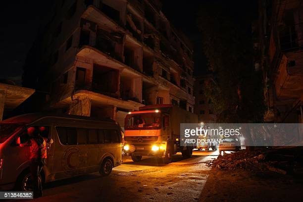 An aid convoy of aid of the Syrian Arab Red Crescent enters the rebelheld town of Saqba on the outskirts of the capital Damascus on March 4 2016 The...